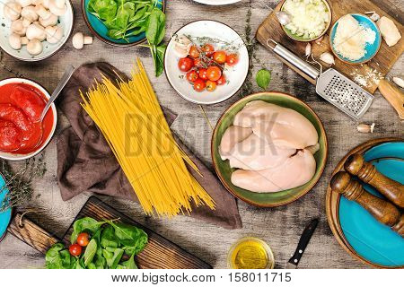 Raw Italian spaghetti with ingredients for preparing pasta on a wooden table top view