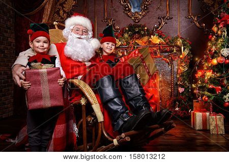 Santa Claus and the elves children with gift boxes. Miracles on Christmas.