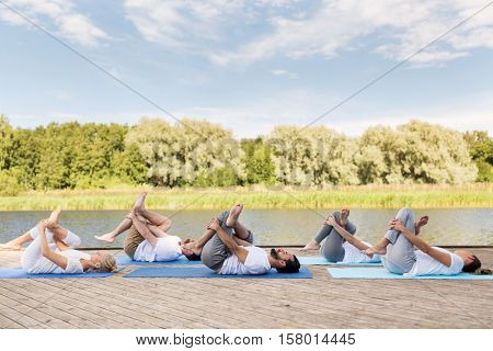 yoga, fitness, sport, and healthy lifestyle concept - group of people making supine pigeon pose on mat outdoors on river or lake berth