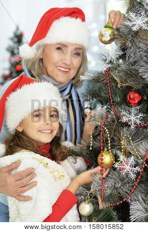 Portrait of smiling grandmother and granddaughter decorating Christmas tree together and looking at the camera