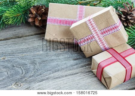 Christmas composition of pine cones spruce branches and stack of gift boxes on the background of old unpainted wooden boards; with copy-space