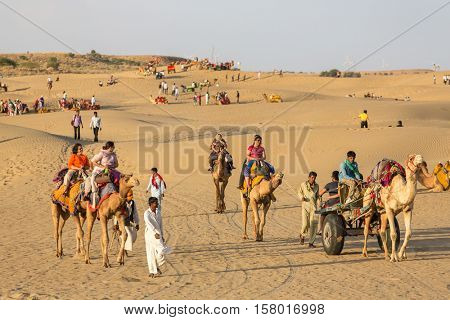 Jaisalmer, India - March 13, 2016: Indian tourists  riding camels in Thar desert, Rajasthan, India