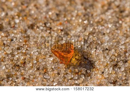 An orange amber on the sand grains