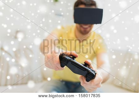 technology, augmented reality, gaming, entertainment and people concept - close up of happy young man with virtual headset or 3d glasses playing video game with controller gamepad at home over snow