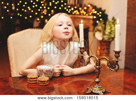 Christmas Child Blowing On Candle Makes A Wish Sitting At The Table Home