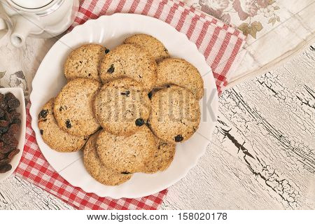 Wholewheat biscuits with raisins on white rustic table. Top view with copy space