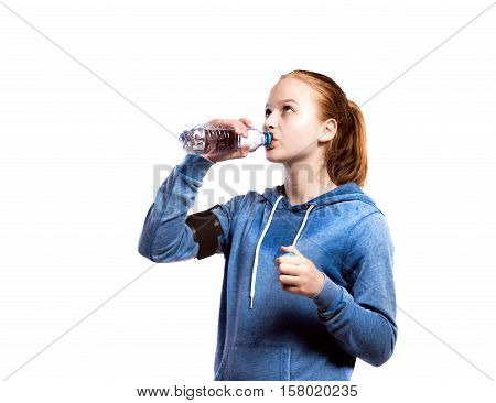 Teenage girl in blue sweatshirt, wearing phone armband, drinking from water bottle. Beautiful young sportswoman, studio shot on white background, isolated.
