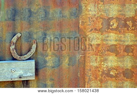 Old Horse shoe resting against rusty patterned corrugated iron shed wall