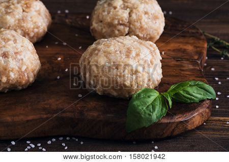 Uncooked Meatballs On A Dark Wooden Board