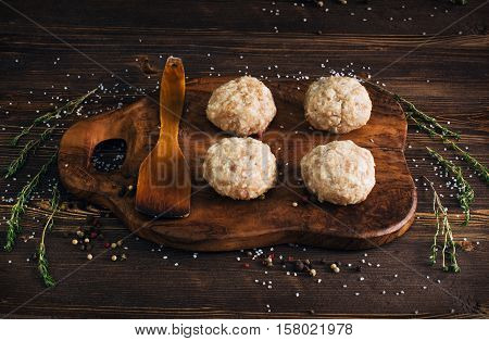 Uncooked meatballs in a dark rustic wooden setting