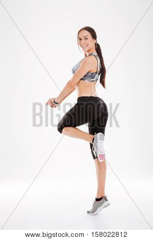 Full length pretty fitness woman in studio. back view. looking at camera. isolated white background