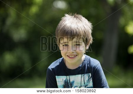 Little laughing boy looks into the camera. Cute boy with a smile on his face. Sunny scene in the garden or in the park. Front view portrait of a rascal child. Youngster scamp with thoughtful face.
