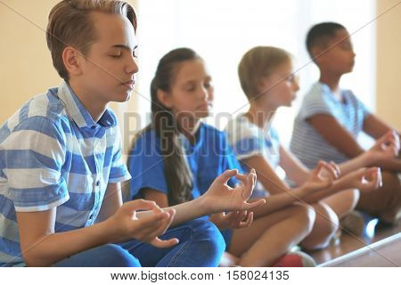 Schoolchildren in lotus position relaxing on lesson