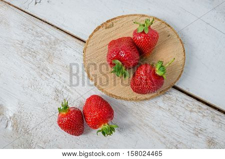 Red berry strawberry on white rustic wooden background. Background from freshly harvested strawberries with space for text. Strawberry background. Directly above. Top view. Copy space.