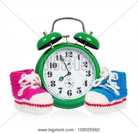 Green alarm clock with  baby boots, isolated on white background
