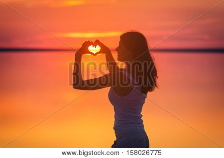 Beautiful female model enjoying sunset and making heart sign on sun at seaside. Calm water of salt lake Elton reflects silhouette of woman. Sun goes under horizon. Girl stands alone in water. Sun reflects in Elton's water.