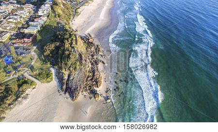 Aerial view looking down at Miami Headland, as the sunrise glow hits the foreshore. Gold Coast, Australia