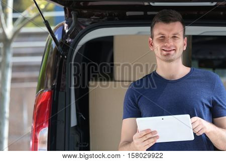 Male deliverer with tablet beside car