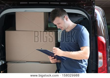 Young male deliverer noting executing of order