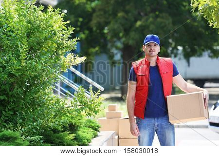 Young male deliverer with box outdoors