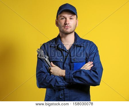 Young mechanic with crossed arms and wrench standing on yellow background