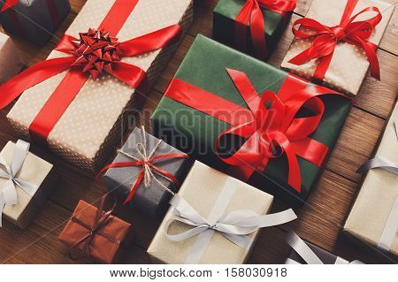 Lots of Gift boxes on wood background. Presents in craft and colored paper decorated with red ribbon bows and snowflakes. Christmas and other holidays concept.