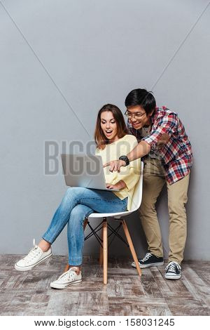 Full length portrait of a young multicultural couple with laptop isolated on the gray background