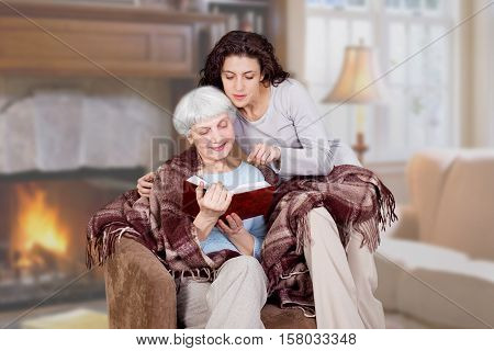 daughter and elderly mother charming read the book in the room with fireplace. grandmother