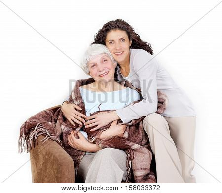 elderly woman and her daughter sitting in a chair with a blanket hug mother grandmother. on a white background
