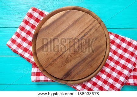 Frame of round cutting board and red plaid tablecloth. Blue wooden background in the restaurant. Copy space