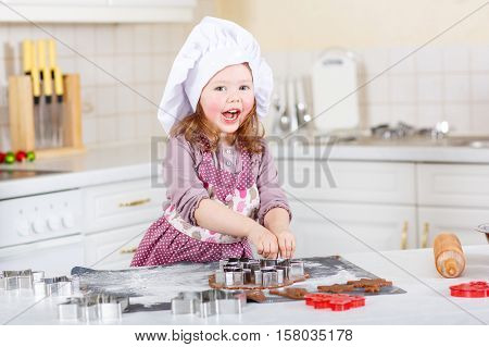 Happy little child, cute kid girl, sitting at the table in domestic kitchen making delicious sweet gingerbread xmas cookies. Kitchen decorated for Christmas holiday. Girl helping and having fun with baking.