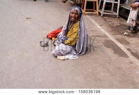 PUSHKAR, INDIA - FEBRUARY 18: Unidentified old indian beggar waits for alms on a street on the ghat along the sacred Sarovar lake in Pushkar, India on February 18, 2016.