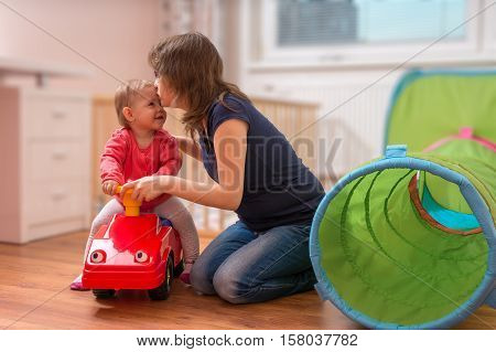 Young Mother Is Playing With Daughter. Woman Is Teaching Her Chi