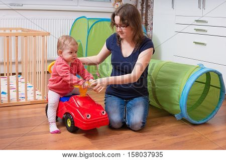 Young Mother Is Teaching Her Child To Drive Toy Car. Woman Is Pl