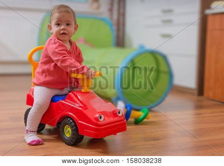 Little Child Girl Is Playing, Sitting On Red Toy Car And Driving