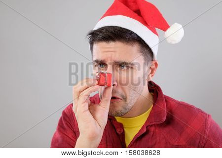 Closeup Portrait Unhappy, Upset Man Holding Small Red Gift