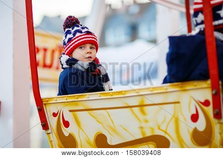 Funny little kid boy on a carousel at Christmas funfair or market, outdoors. Happy child having fun. Traditional xmas market in Germany, Europe. Holiday, children, lifestyle concept.