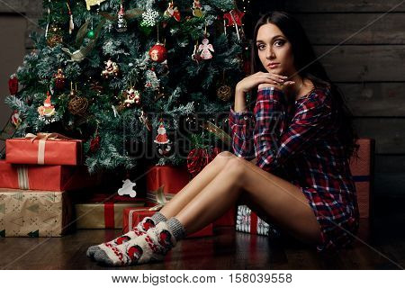 woman with long black hair posing under christmass tree in man shirt