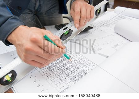 Closeup of man's working with blueprints at construction site