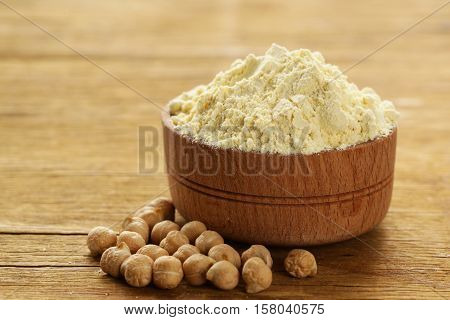 Natural organic chick pea flour in a wooden bowl