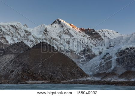 Beautiful Sunset Over Mountain Cho Oyu Reflecting In The Gray Moraine Lake Covered With Ice. Amazing