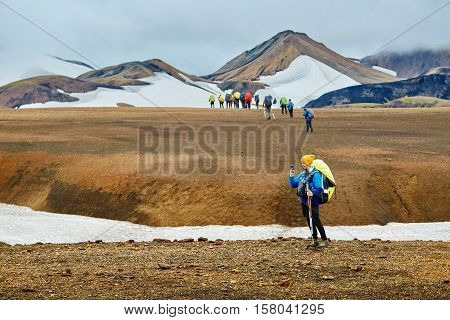 hikers on the trail in the Islandic mountains. Trek in National Park Landmannalaugar, Iceland. Hiker shooting landscape