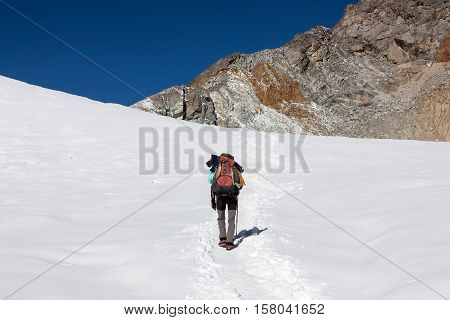 Extreme Solo Hiking Concept. Single Traveller Walking Up The Mountain In Deep Snow With Big Heavy Ba