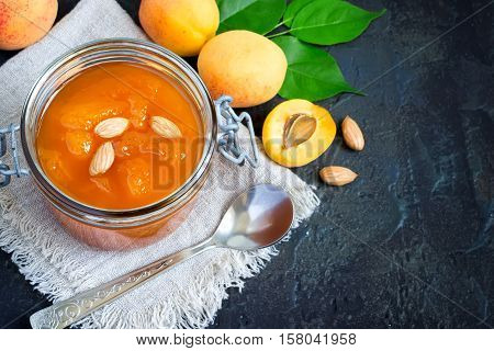 Fresh apricot jam in jar and ripe apricots. Top view with copy space