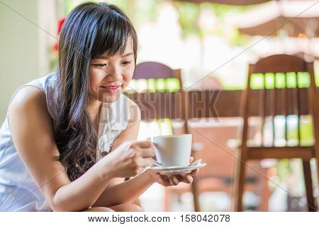 Asian Woman Sitting On Sofa With Coffee
