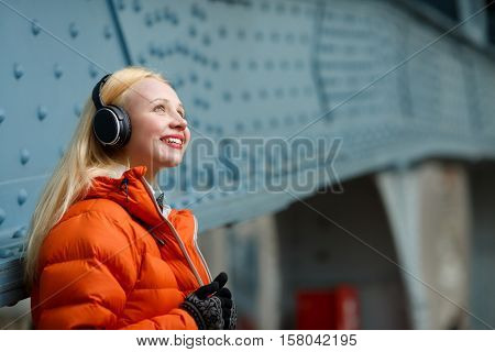 Ginger in orange jacket enjoying music on headphones indoors