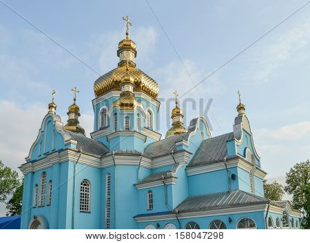 Gorodok, Ukraine - May 14, 2013: Blue colored orthodox church in small town in Rivne oblast or region with gold cupola and tiled floor