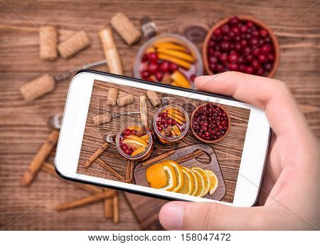 Hands taking photo homemade mulled wine with orange slices, cranberries, cinnamon with smartphone.