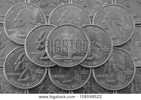 Coins of USA. Pile of the US quarter coins with George Washington and on the top a quarter of Connecticut State.