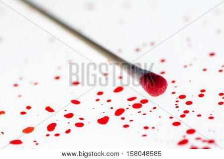 Cotton swab and blood drips in crime scene investigation close up with selective focus